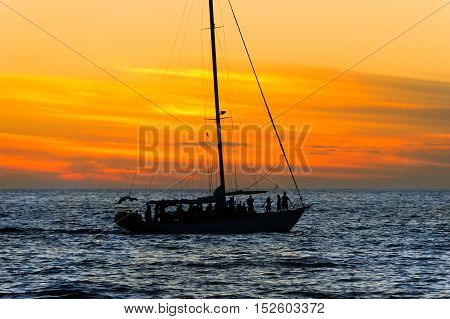 Sunset sailboat party is a group of people having a good time ocean sailing at sunset.
