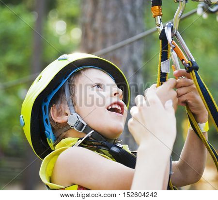 little cute boy in helmet runs track in green forest, happy smiling brave kid alone training, lifestyle people concept close up