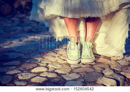 Bride's Legs in Sneakers. Modern Youth Hipster Style Wedding Concept. Toned and Filtered Photo with Copy Space.