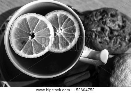 A cup of tea with lemon pieces and cookies on the table - black and white.