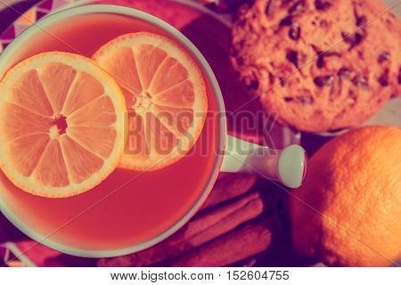 A cup of tee with lemon and cookies.