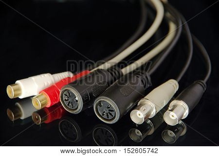 Many different audio connectors with reflection isolated on black background.