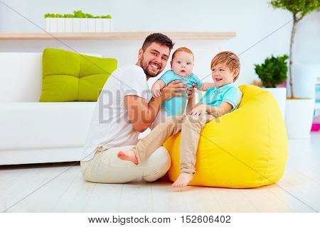 Happy Father With Six Month And Six Years Old Sons, At Home
