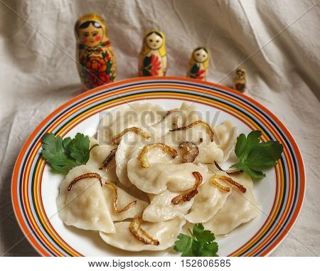 Russian vareniki with potato and fried onion with matreshkas on the background