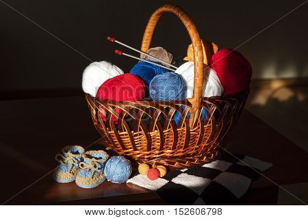 basket with rolls of colored thread is on the table in a beam of light