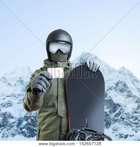 Snowboarder holding blank lift pass with mountain on background