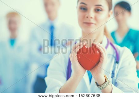 Young woman doctor holding a red heart
