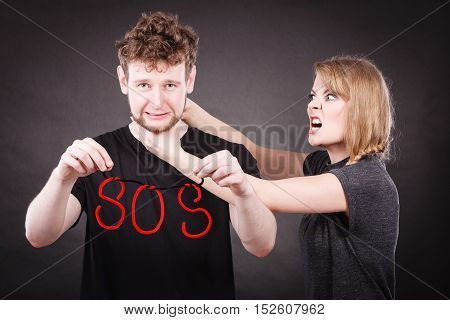 Betrayal and break up in relationship. Young couple arguing and holding red sos word sign symbol. Blonde woman in fury yelling on man. Negative emotions.