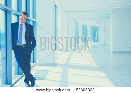 Successful businessman standing in hallway his company near window