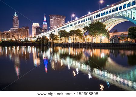 Cleveland city skyline and Detriot-Superior Bridge at night across the Cuyahoga river