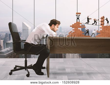 Businessman watches a teamwork of businesspeople work together to a bricks construction