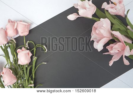 Flat composition with text place and rose flower. Gentle romantic photo background for love letters. Table top view with white and black paper. Floral decor mockup