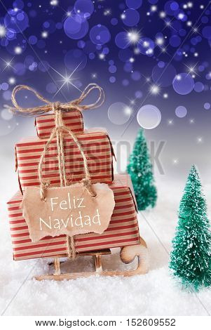 Vertical Image Of Sleigh Or Sled With Christmas Gifts Or Presents. Snowy Scenery With Snow And Trees. Blue Sparkling Background With Bokeh. Label With Spanish Text Feliz Navidad Means Merry Christmas