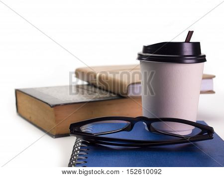 closeup of glasses and books and coffee cup Put on a white background