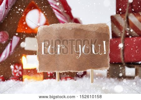 Gingerbread House In Snowy Scenery As Christmas Decoration. Sleigh With Christmas Gifts Or Presents And Snowflakes. Label With English Text For You