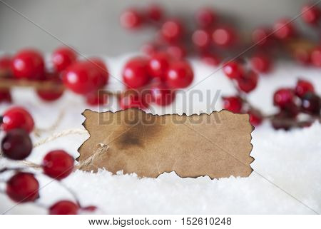 Burnt Label With Copy Space For Advertisement. Red Christmas Decoration On Snow. Cement Wall As Background. Card For Seasons Greetings