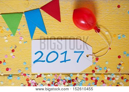 White Label With 2017 For Happy New Year. Party Decoration Like Streamer, Confetti And Balloon. Flat Lay Or Top View. Yellow Wooden Background