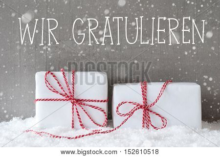 German Text Wir Gratulieren Means Congratulations. Two White Christmas Gifts Or Presents On Snow. Cement Wall As Background With Snowflakes. Modern And Urban Style.