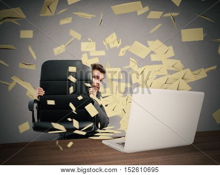 Scared businessman hidden behind the chair submerged by the mail
