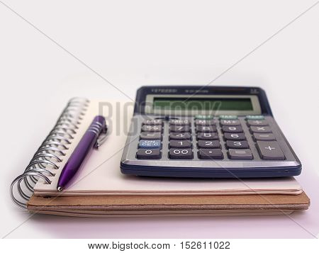 Business concept with notebook pen and calculator White background.