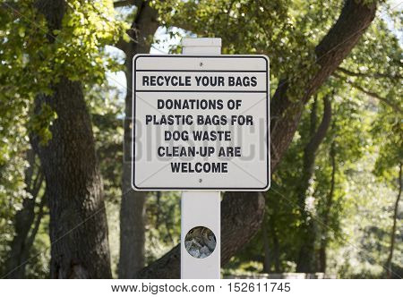 A sign in a dog walking park to donate plastic bags for waste clean-up.