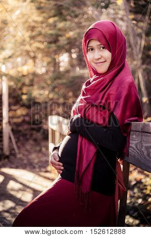 A pregnant muslim woman with natural background during autumn season
