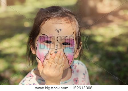 Cute girl getting face paintied as a butterfly