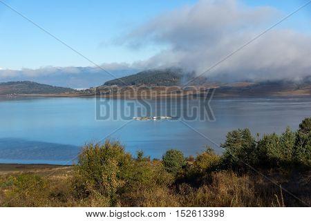Landscape with Low clouds over water of Batak Reservoir, Pazardzhik Region, Bulgaria