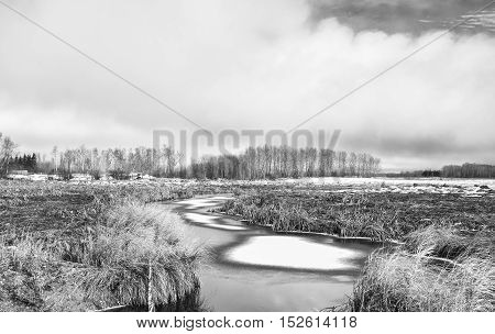 A stream dotted with snow patches winding through a harvested field under cloudy sky in rural black and white landscape