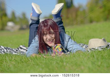 beautiful young woman in jeans lying on the grass in park