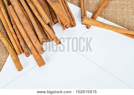 Cinnamon sticks with empty space of white paper for your text or message on sack background.