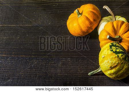 Orange and yellow pumpkin on black rustic wooden table.