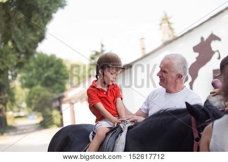a little boy sitting on top of a black horse listening to his grandfather's instruction