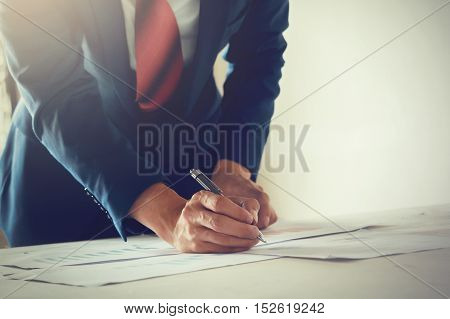 Businessman In Suit Writing On Work Desk