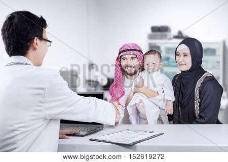 Image of Arabian father and his family visiting pediatrician while handshake and sitting in the clinic room