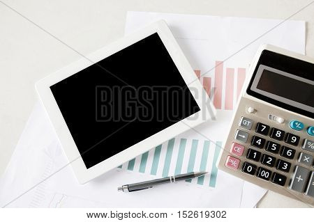 Blank Digital Tablet On Stock And Finance Graph Papers On Desk With Calculator And Pen- With Copy Sp