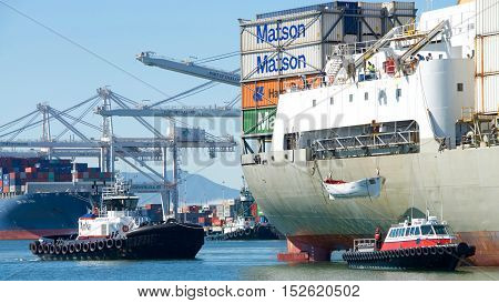 Oakland CA - September 27 2016: Tugboat FALCON off the starboard quarter of cargo ship KAUAI awaiting lowering of lifeboat to be taken for service prior to the vessel docking at the Port of Oakland.