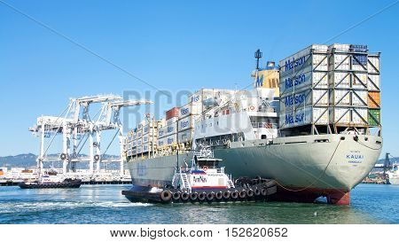 Oakland CA - September 27 2016: Tugboat PATRICIA ANN pulling on the bow REVOLUTION pushing on the stern to rotate Matson cargo ship KAUAI 180 degrees to dock at the Port of Oakland