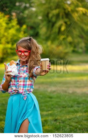 Pretty attractive girl holds cup of coffee and a hot dog in a park. Snack. Fast food.