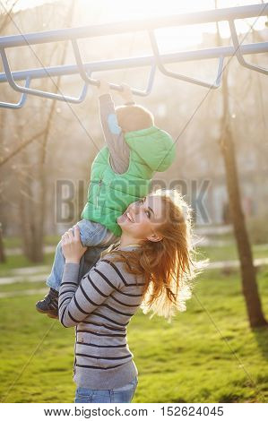 Mom helps son to the horizontal bars in the autumn park. Family time. Happiness of childhood and parenthood. Outdoor Activities.