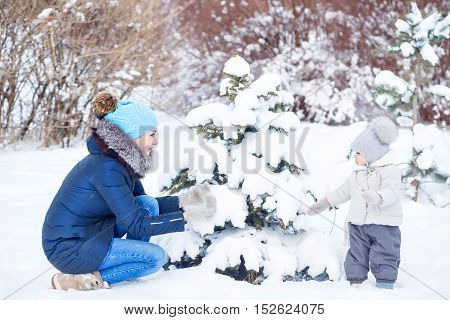 Mother and little daughter in a winter park. Mother and daughter play at the Christmas tree. Happy family. Childhood and parenthood happiness.