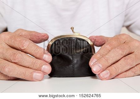Old senior hands and small retro styled money pouch