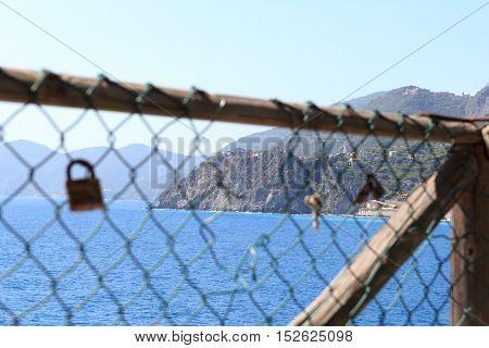 Padlocks And Rocky Coast With Cinque Terre Village Corniglia And Mediterranean Sea, Italy