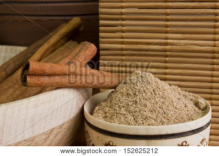 Powdered cinnamon and sticks on bamboo napkin background