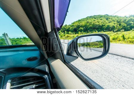 Reflection of sunny autumn road at the car side mirror