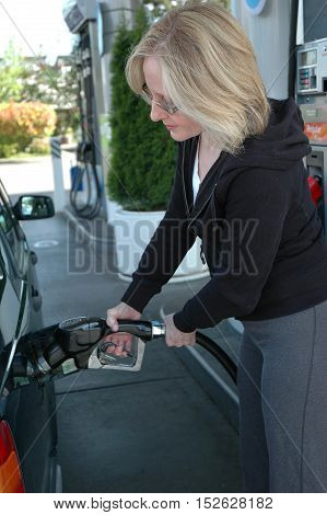 Mature female blond beauty pumping gas into her car.