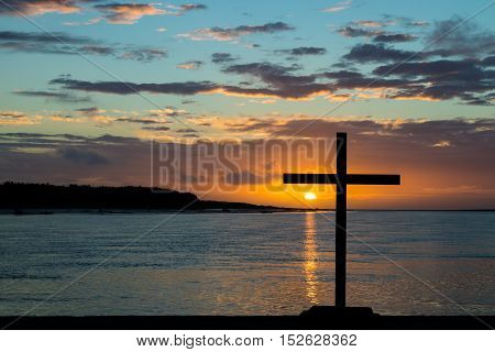 Black cross with a sunset at a river mouth area.