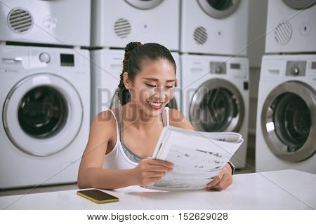 Lovely Asian young woman reading newspaper in laundromat