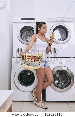 Young woman with basket of dirty clothes standing in laundromat