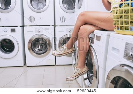 Legs of young woman sitting on washing machine